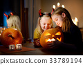 Two pretty young sisters in halloween costumes carving a pumpkin together 33789194