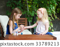 Adorable little girls having fun playing at home with colorful nail polish 33789213