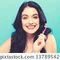 Young woman holding a toothbrush  33789542
