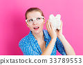 Young woman with a piggy bank 33789553