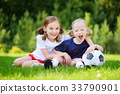 Two cute little sisters having fun playing a soccer game 33790901