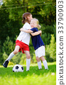 Two cute little sisters having fun playing a soccer game 33790903