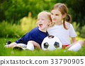 Two cute little sisters having fun playing a soccer game 33790905