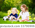 Two cute little sisters having fun playing a soccer game 33790906