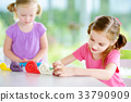 Two cute little sisters having fun together with colorful modeling clay at a daycare 33790909