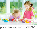 Two cute little sisters having fun together with colorful modeling clay at a daycare 33790926