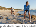 Young couple on beach training together 33797440