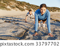 Young couple doing push ups on ocean beach 33797702
