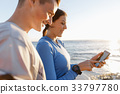 Young couple with smartphones outdoors 33797780