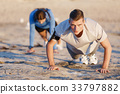 Young couple doing push ups on ocean beach 33797882