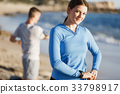 Young couple on beach training together 33798917
