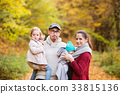 Beautiful young family on a walk in autumn forest. 33815136