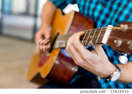 Man playing guitar in office 33828930