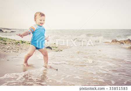 One year old boy is playing on the beach 33851583