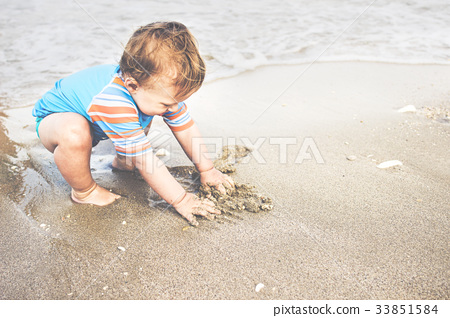 One year old boy is playing on the beach 33851584