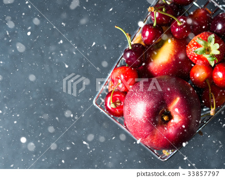 Fresh fruit in supermarket cart on black. Snow 33857797