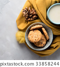 Mug of tea with milk and cookies in winter scarf 33858244