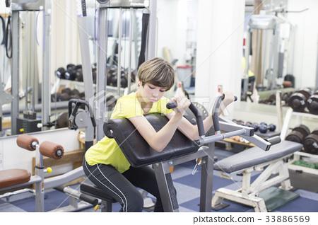 오사카 시내의 헬스장에서 운동기구를 사용하여 팔 운동을하고있는 하프 젊은 여성 33886569
