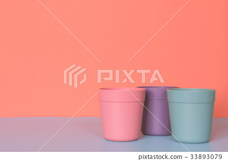 Three color plastic cup on colors background. 33893079