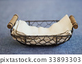 Tissue napkin in metal basket on blue fabric table 33893303