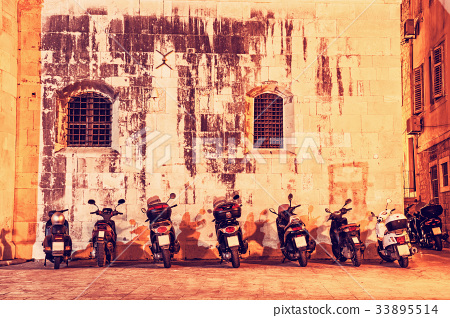 Motorbike parking near wall of Trogir cathedral 33895514