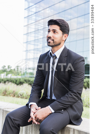 Successful businessman or worker sitting in suit 33899484