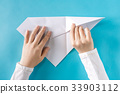 Person's hands folding a paper airplane 33903112