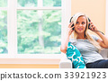 Happy young woman listening to music on headphones 33921923