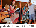 Hippie friends with guitar on a road trip 33922906