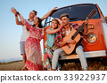 Hippie friends with guitar on a road trip 33922937