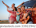 Hippie friends with guitar on a road trip 33922942