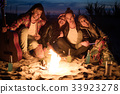 Hippie friends with guitar near bonfire 33923278