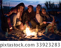 Hippie friends with guitar near bonfire 33923283