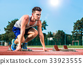 Track and field sprinter on starting point at 33923555