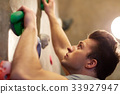 young man exercising at indoor climbing gym wall 33927947