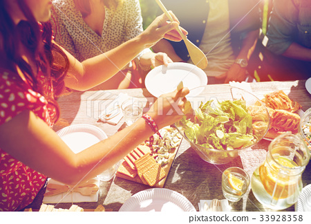 happy friends having dinner at summer party 33928358