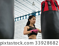 young woman execute exercise in fitness center. female athlete hitting and punching sandbag with rowing machine in boxing gym. sporty girl working out in health club. martial arts, muay thai concept 33928682