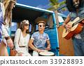 hippie friends playing music over minivan on beach 33928893