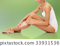 woman removing leg hair with depilatory wax strip 33931536