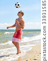 young man with ball playing soccer on beach 33931585