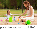 happy mother and baby girl playing in sandbox 33931620