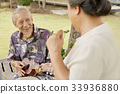 an old man is playing ukulele and smiling with his wife 33936880