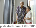 senior woman is assisting her husband to walk with cane 33936905