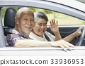 smiling senior couple is driving on a car and waving 33936953