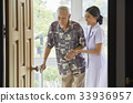 a nurse and senior man are smiling and walking indoors 33936957