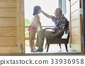 a senior man is sitting on bench and talking with his granddaughter 33936958