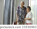 senior couple is standing and looking at something from window 33936963