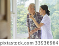 a smiling nurse is pointing something for a senior patient 33936964