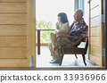a grandfather and a child are sitting and looking at something 33936966