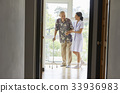 a nurse and a senior man are walking and smiling indoors 33936983